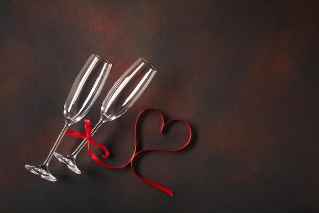 Cartão do dia de valentim com vidros do champanhe e corações dos doces no fundo de pedra. Foto Premium