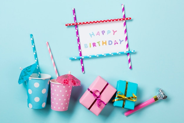 Cartão do feliz aniversario perto dos vidros dinking; caixas de presente e chifre de ventilador no pano de fundo azul Foto gratuita