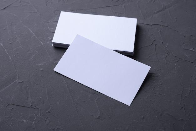 Cartão em branco na parede de rocha beton. artigos de papelaria corporativos. mesa de designer criativa. postura plana. copie o espaço para o texto. Foto Premium