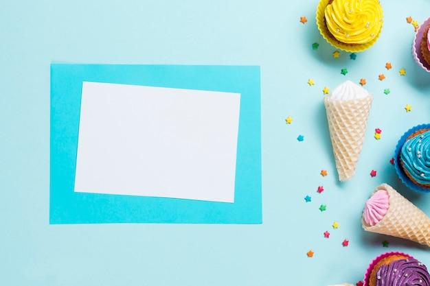 Cartão em branco perto do polvilho; cones de waffle e muffins em pano de fundo azul Foto gratuita