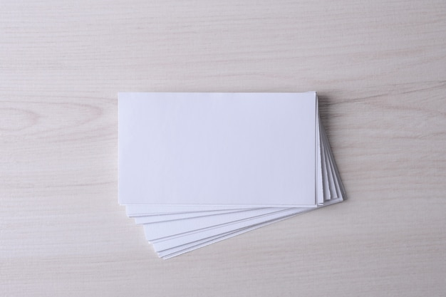 Cartão em branco sobre fundo de madeira. artigos de papelaria corporativos, mock-up de branding. mesa de designer criativa. postura plana. copie o espaço para o texto. modelo de id. Foto Premium