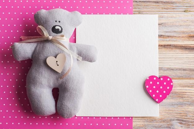 Cartão em branco sobre fundo rosa com ursinho de pelúcia Foto Premium