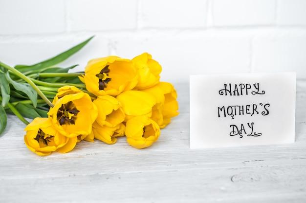 Cartão para dia das mães e tulipas amarelas na mesa de madeira Foto Premium