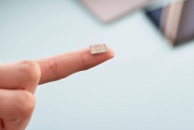 Cartão sim de close-up na ponta do dedo Foto gratuita
