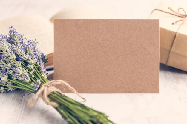 Cartão vazio de kraft do cumprimento na frente de um ramalhete da alfazema, de um presente envolvido e de um livro velho sobre um fundo de madeira branco. Foto Premium