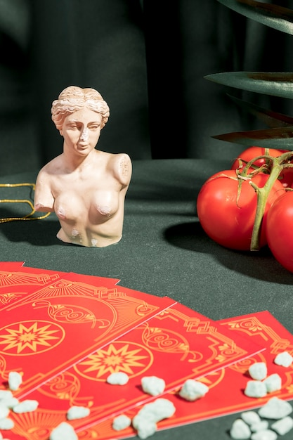 Cartas de tarô ao lado do busto e dos tomates Foto gratuita
