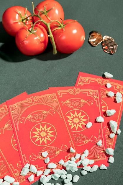 Cartas de tarô de alto ângulo ao lado de tomates Foto gratuita