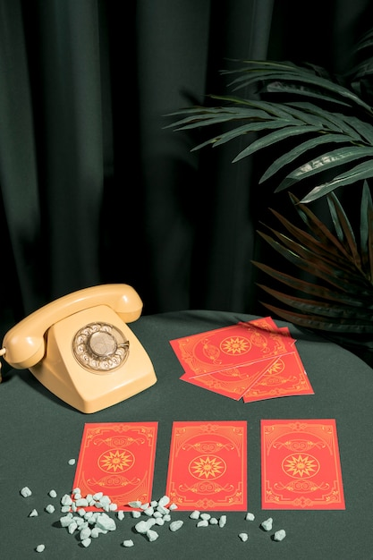 Cartas de tarô para boa sorte ao lado de telefone retro Foto gratuita