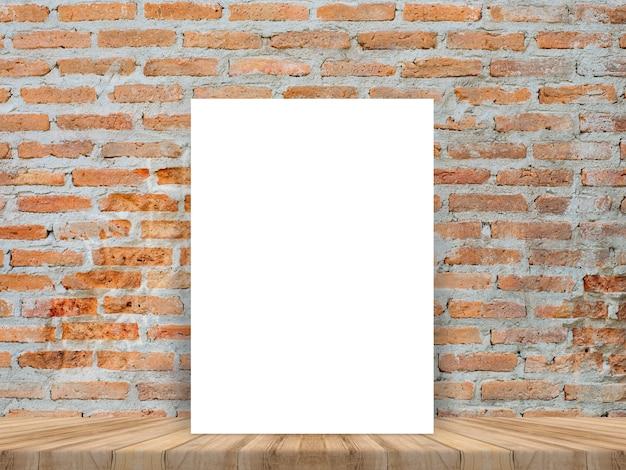 Cartaz branco em branco inclinado na mesa de madeira tropical com parede de tijolos Foto gratuita