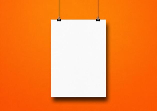 Cartaz branco pendurado em uma parede laranja com clipes. modelo de maquete em branco Foto Premium