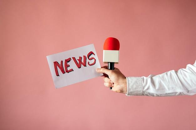 Cartaz com a palavra da notícia e microfone na mão do repórter com parede rosa Foto Premium