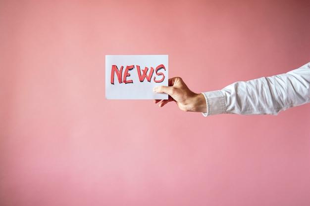Cartaz com a palavra da notícia na mão do repórter com fundo rosa Foto Premium