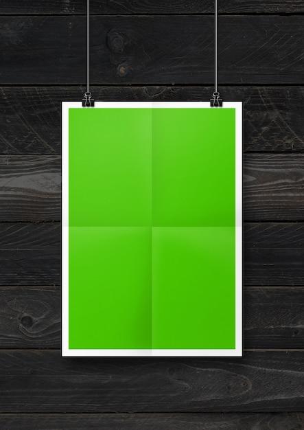 Cartaz dobrado verde pendurado em uma parede de madeira preta com clipes. modelo de maquete em branco Foto Premium