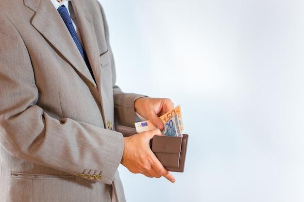 Carteira de couro com dinheiro em mãos de homem de negócios em branco Foto Premium