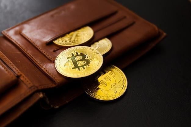 Carteira de couro marrom com metal bitcoins em fundo preto. Foto Premium