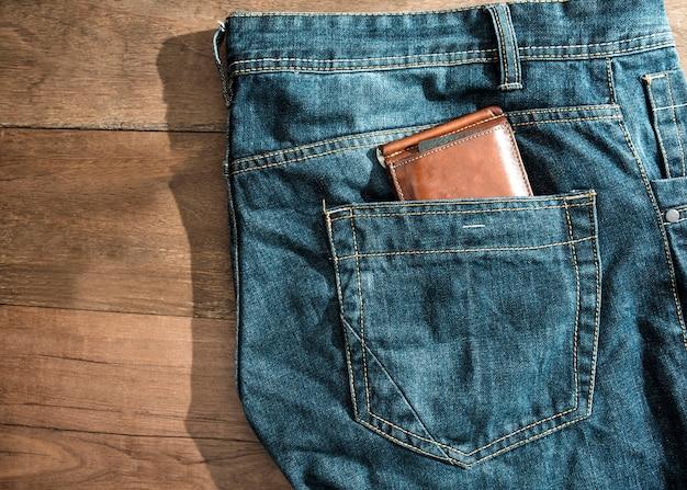 Carteira de couro marrom no bolso de trás jeans azul. Foto Premium