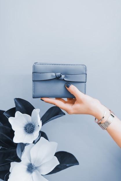 Carteira elegante feminina nas mãos de uma menina com uma manicure azul escuro. a cor do ano 2020. Foto Premium
