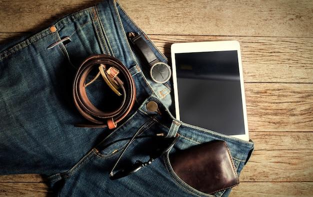 Carteira jeans e cinto relógios óculos no fundo de madeira, vista superior Foto Premium