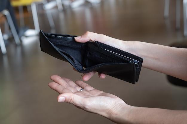 Carteira vazia nas mãos da mulher. Foto Premium