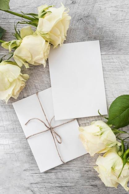 Cartões de casamento com rosas em fundo de madeira Foto gratuita