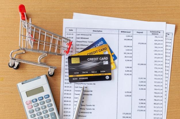 Cartões de crédito e carrinho de supermercado e calculadora no extrato bancário em uma mesa de madeira Foto Premium