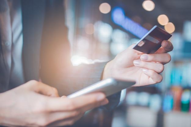 Cartões e smartphones de crédito do uso da mão da mulher de negócio. Foto Premium