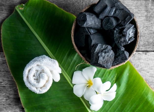 Carvão vegetal em casca de coco para spa no fundo de madeira com toalha branca e flor na folha de bananeira Foto Premium