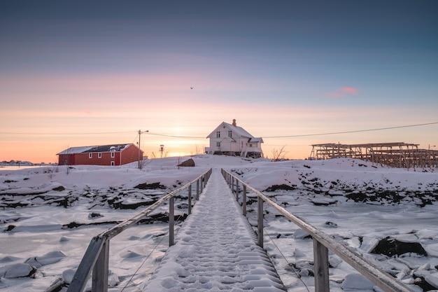 Casa branca com ponte de madeira e costa congelada Foto Premium