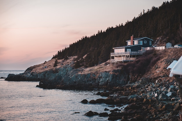 Casa branca e marrom na montanha rochosa marrom ao lado do corpo de água durante o dia Foto gratuita