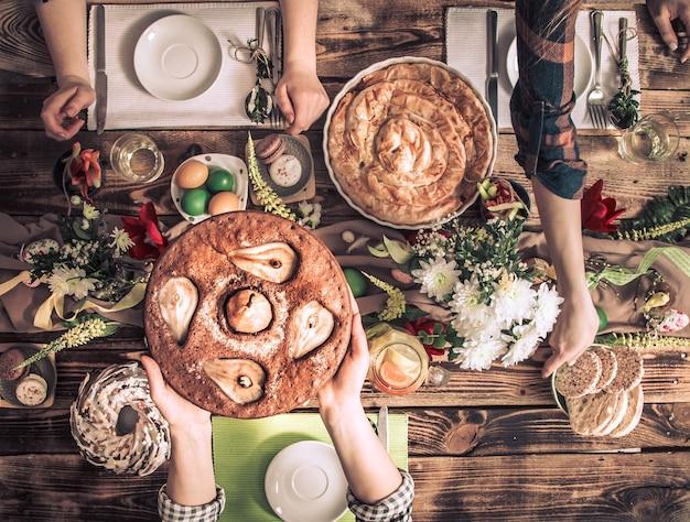 Casa celebração de amigos ou familiares na mesa festiva com bolo de pêra, vista de cima, celebração. conceito Foto gratuita