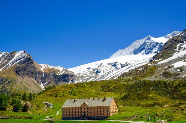 Casa cercada por montanhas rochosas cobertas de vegetação e neve em valais, na suíça Foto gratuita
