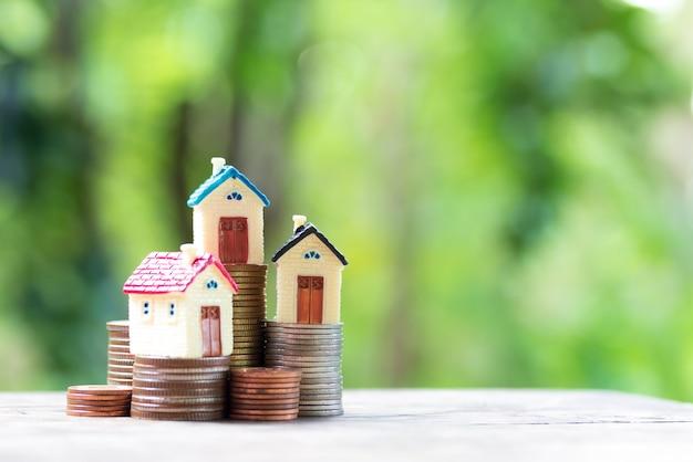 Casa colorida em miniatura na pilha de moedas usando como propriedade e conceito de finanças Foto Premium
