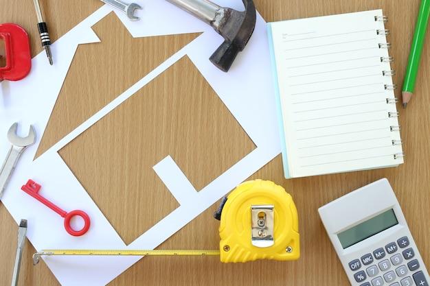 Casa dada forma de papel em um fundo da ferramenta marrom da madeira e do artesão. Foto Premium