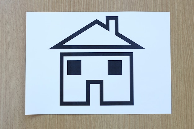 Casa dada forma papel em um fundo da madeira marrom. Foto Premium