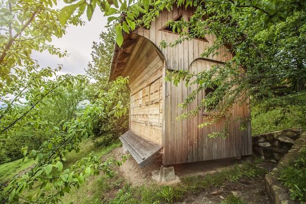 Casa de abelhas de madeira cercada por árvores no campo Foto gratuita