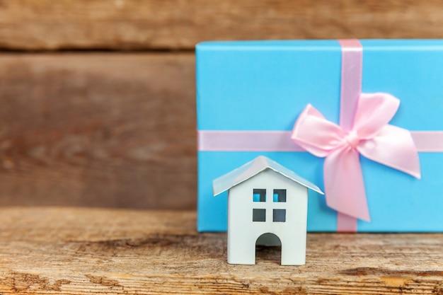 Casa de brinquedo branca em miniatura e caixa de presente embrulhada em papel azul em fundo de madeira Foto Premium