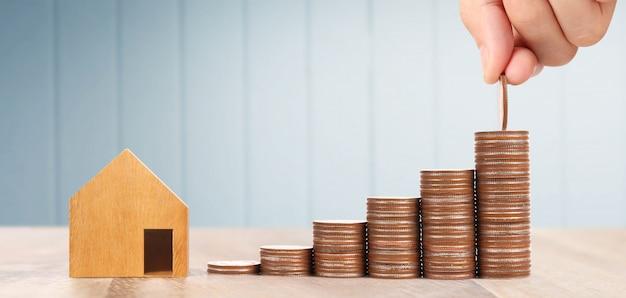 Casa de brinquedo de madeira conceito de casa de propriedade de hipoteca comprando para a família, moedas na mão Foto Premium