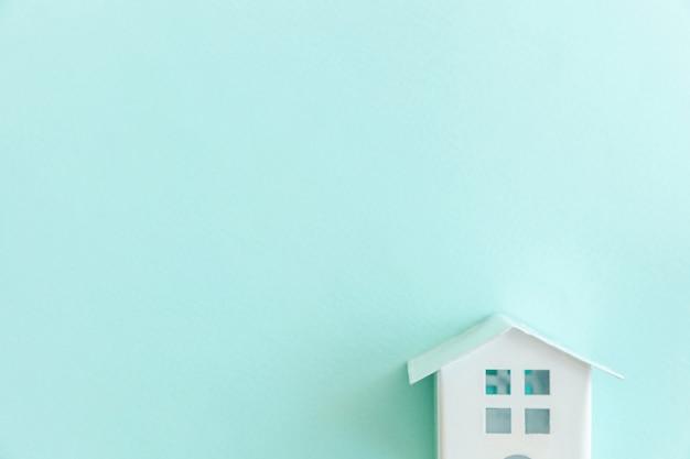 Casa de brinquedo em miniatura branca sobre fundo azul pastel Foto Premium