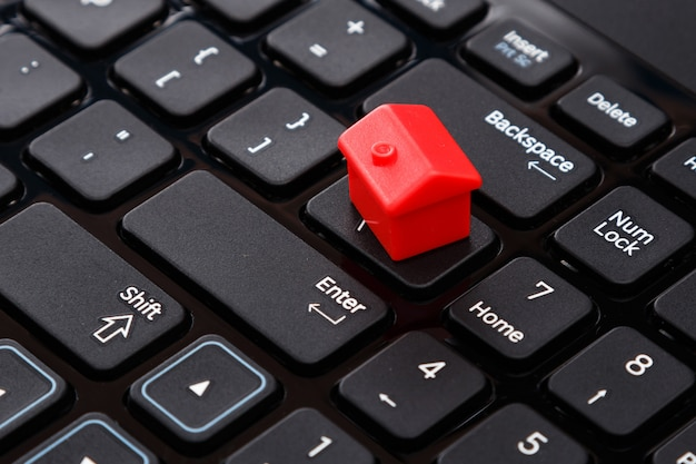 Casa de brinquedo pequeno sobre o teclado Foto Premium
