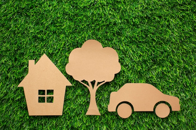 Casa de carro dos desenhos animados e árvore na grama Foto gratuita