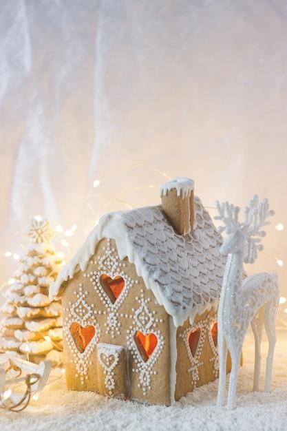 Casa de gengibre, árvores de natal e uma figura de um cervo em um fundo luminoso. efeito bokeh. Foto Premium