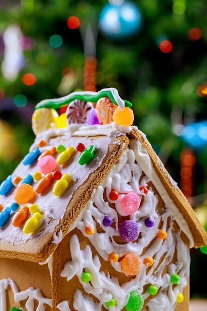 Casa de gengibre decorada na frente de uma árvore de natal. Foto Premium