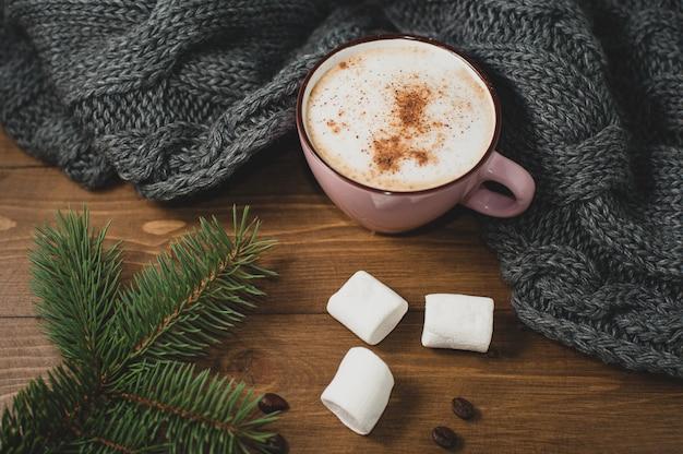 Casa de inverno aconchegante. xícara de chocolate com marshmallow, cachecol de malha quente e raminho de árvore de natal, grãos de café na mesa de madeira marrom. Foto Premium