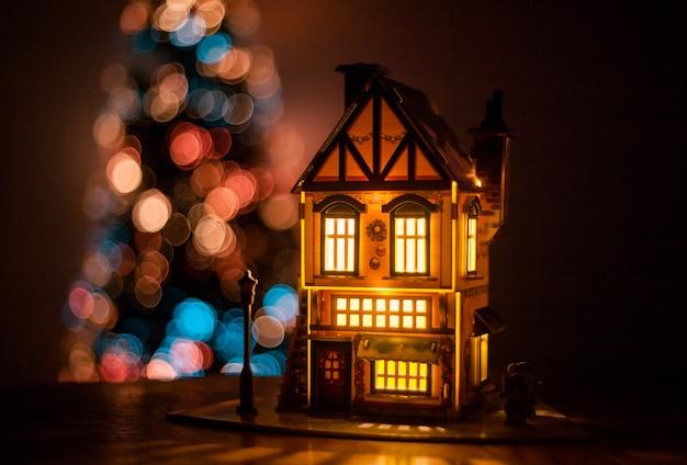 Casa de inverno feita de papelão feita com as mãos na mesa, casa luminosa, decoração para o ano novo e natal Foto Premium