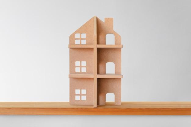 Casa de madeira do brinquedo em uma prateleira de madeira. símbolo de imóveis. Foto Premium