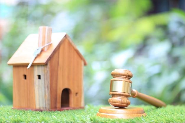 Casa de madeira e modelo de martelo sobre fundo verde natural Foto Premium