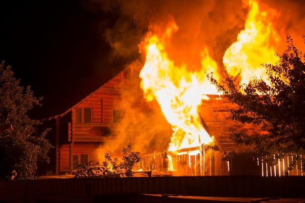 Casa de madeira em chamas à noite Foto Premium