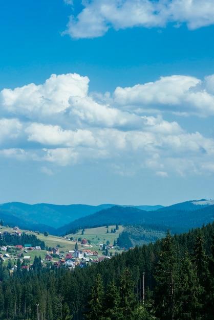 Casa de madeira nas montanhas verdes com céu azul e nuvens Foto gratuita