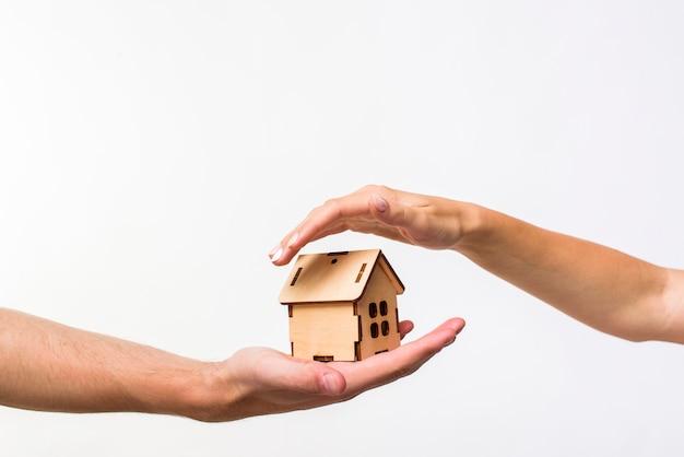Casa de madeira protegida por mãos Foto Premium