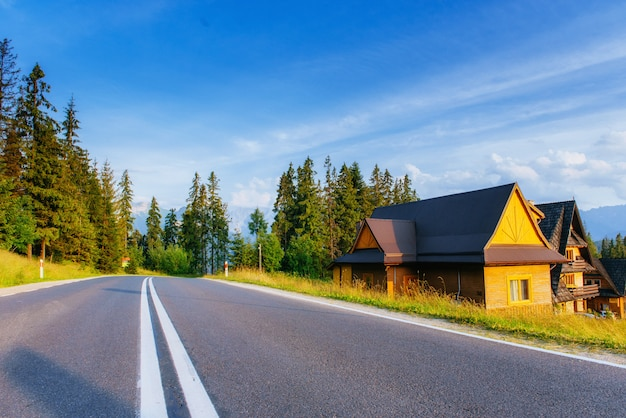 Casa de madeira tradicional nas montanhas em campo verde Foto Premium